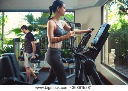 Woman Exercising At The Gym In An Elliptical Trainer. Young Woman Doing Cardio Training
