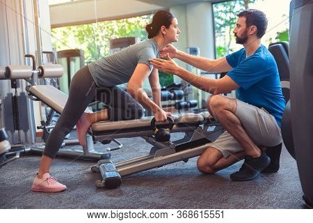 Personal Trainer Working With Client In Gym. Trainer Man Helping Woman Work Out With Dumbbells