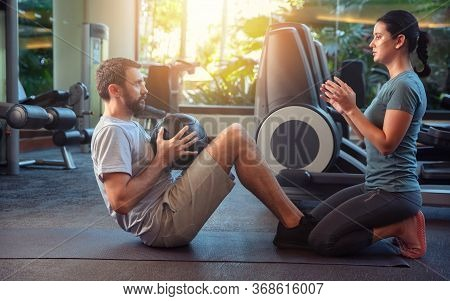 Personal Trainer Working With Client In Gym. Trainer Woman Helping Man With His Abs Workout