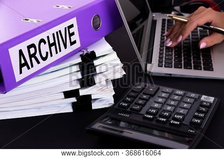 Text, Word Archive Is Written On A Folder Lying On Documents On An Office Desk With A Laptop And A C
