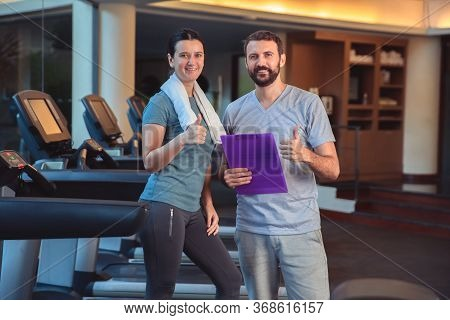 Personal Trainer Working With Client In Gym. Trainer Man Giving Advises And Discussing Results With
