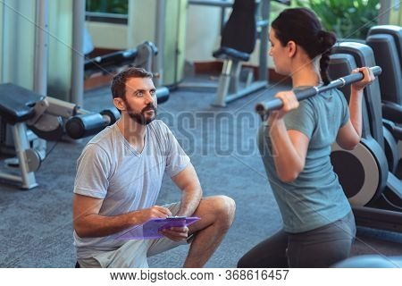 Personal Trainer Working With Client In Gym. Trainer Man Helping Young Woman With Butt Dumbbell Work