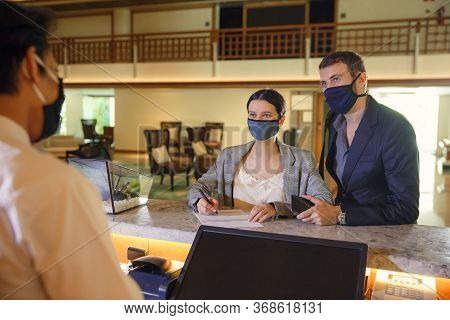Couple And Receptionist At Counter In Hotel Wearing Medical Masks As Precaution Against Virus. Coupl