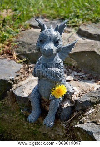 Sitting Dragon Guarding A Well On A Stone With A Dandelion