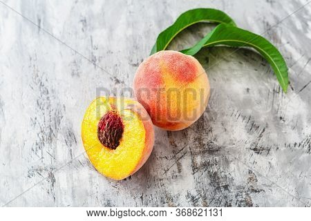 Peach And Half Peach With Leaf On Gray Concrete Background. Fresh Sweet Peach With Pitted. Top View