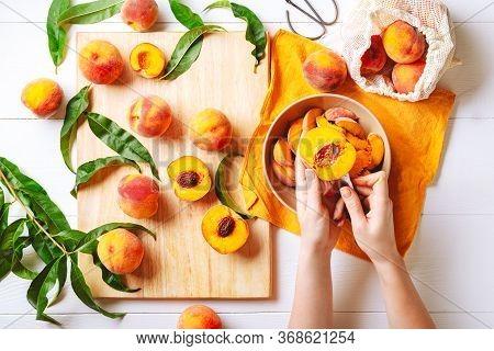 Female Hands Cutting Fresh Sweet Peaches. Peaches Whole Fruits Leaves, Half Peach, Peach Slices On W