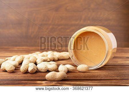 Creamy Peanut Paste In Open Glass Jar, Peanut Butter Spoon, Peanuts And Peanuts In The Peel Scattere