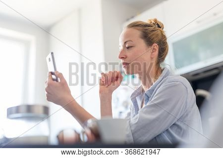 Young Pleased Woman Indoors At Home Kitchen Using Social Media Apps On Mobile Phone For Chatting And