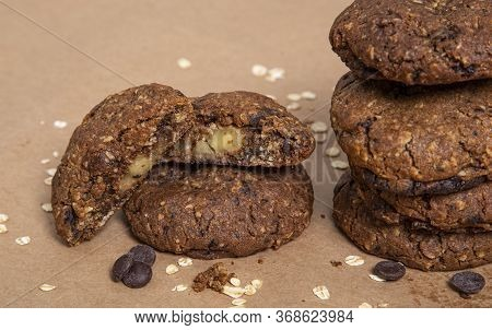 Oatmeal Chocolate Chip Cookie Filled With Apple With Oatmeal And Chocolate Shavings On Paper Backgro