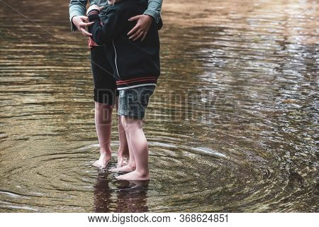 Children Playing Together In Water Outside In A Stream During A Warm Day