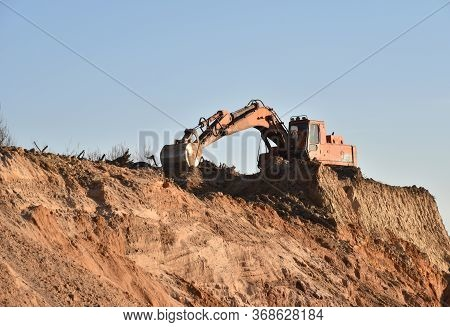Large Excavator Working At Construction Site. Backhoe During Earthworks On Sand Quarry. Earth-moving