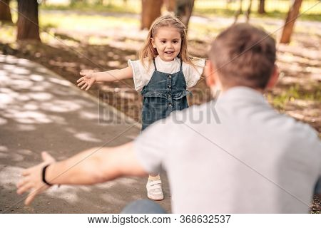 Dad With Little Daughter Play In The Park On The Street, Toddler Runs To Meet Dad, Child Hugs Dad, C