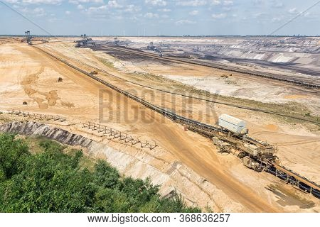 Brown Coal Open Pit Landscape With Enormous Digging Excavators In Garzweiler Mine Germany