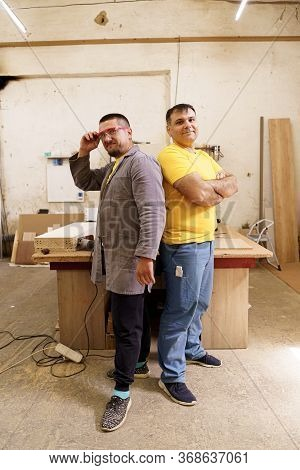 Confident Carpenters Near Their Workbench In Their Workshop Looking To Camera