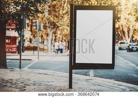Mockup Of An Empty Ad Billboard In Urban Settings Near A Road Junction; A Blank Vertical Street Bann