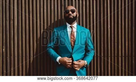 A Handsome Mature Bald Bearded African Man In A Sunglasses And A Fashionable Blue Or Teal Costume Wi