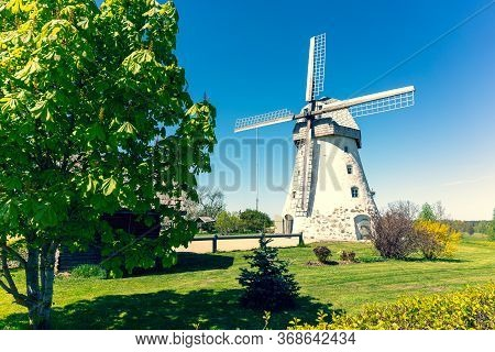 Ancient Mill With Wings On A Green Hill Of Latvia In Spring. Near The Mill Is A Nest Of Storks. Gauj