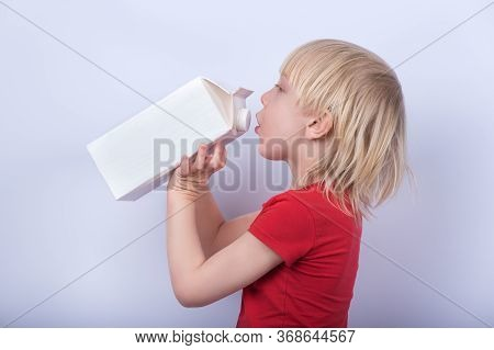 Fair-haired Boy Drinking Milk Or Juice From Large Carton. Portrait Of Child With Carton Of Milk On W