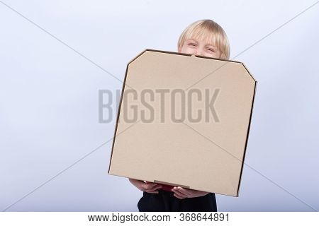 Child Holding Box Of Pizza And Laughs. Fair-haired With A Box In His Hands. Pizza Delivery.