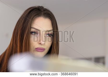 Natural Brunette Putting On Makeup, Waiting To Dry. Worried Distant Look, Seen Behind A Mirror