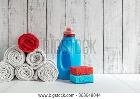 Clean Laundry And Liquid Washing Detergent,  Pile White Towels On White Desk And Liquid Laundry Dete