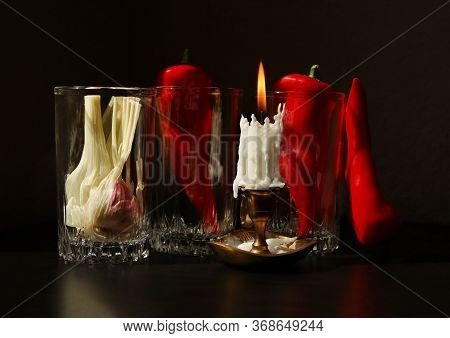 Still Life With Candlestick With Burning Candle, Red Ramiro Peppers And Garlic Bulb In The Glass Bea