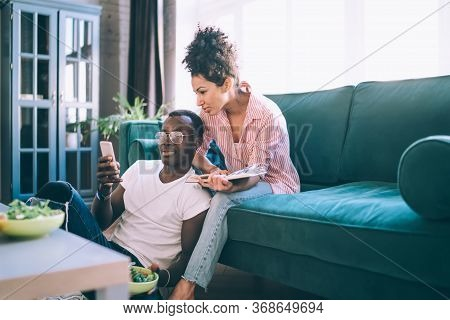 Cheerful Couple Spending Time At Home With Phone
