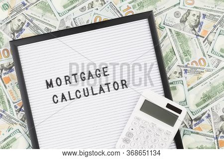Mortgage Calculator Text On Letter Board With Lots Of Hundred Dollar Bills As Background. Mortgage I