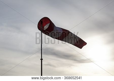 Striped Red And White Windsock On The Pole Fluttering In The Wind On The Cloudy Sky And Down Sun Bac