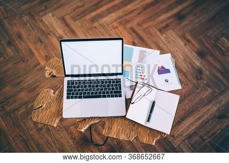 Laptop Next To Notebook And Documents On Coffee Table At Home
