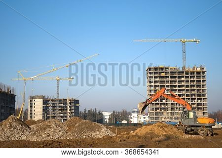Bucked Wheel Excavator Digs Ground At A Construction Site For Installing Concrete Storm Pipes. Backh