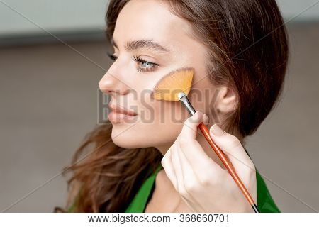 Makeup Artist Applies Dry Cosmetic Tonal Foundation On The Face Using Make Up Brush. Perfect Natural