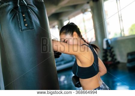 Attractive Asian Female Punching A Black Bag With Boxing Gloves On In Gym