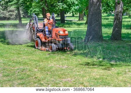 Man Mows The Grass Under Trees In Park By Riding Mowing Machine In Sunny Day