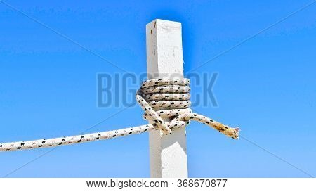 White Wooden Stake With Colored Rope Wrapped Around In Contrast To The Clear Blue Sky