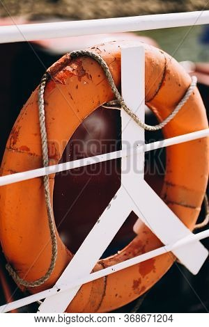 Buoy Or Lifebuoy Ring On Shipboard In Evening Sea. Flotation Device On Ship Side On Seascape. Safety