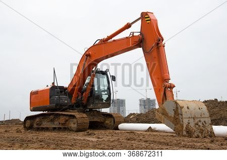 Excavator During Earthworks At Construction Site. Backhoe Digging The Ground For The Foundation And