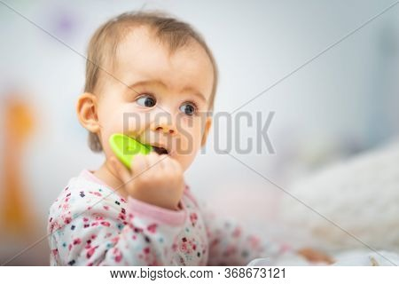 Sweet 1 Year Old Baby Girl Portrait With Rubber Chew Toy In Her Bright Room. Copy Space On Right
