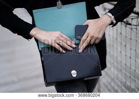 Trendy Woman Holding Her Fashion Small Bag Or Clutch. Dark Clutch In Hands. Trendy Girl Near Wooden