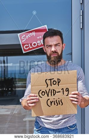 Unemployed Guy With Sign Stop Covid-19 Crisis Near Closed Door Office Or Cafe. Unemployment During C