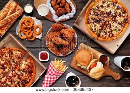 Buffet Table Scene Of Take Out Or Delivery Foods. Pizza, Hamburgers, Fried Chicken And Sides. Above