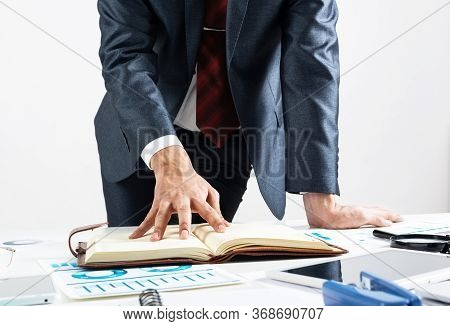 Businessman Analyzing Financial Documents At Office Desk. Financial Expertise And Consulting. Manage