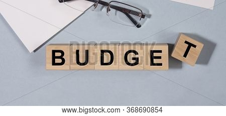 Word Budget On Wooden Cubes, Glasses And Planner On Office Table. Business Economy Budgeting And Pla