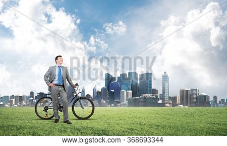 Good Looking Caucasian Man In Business Suit Posing On Green Meadow With Bike. Happy Businessman With