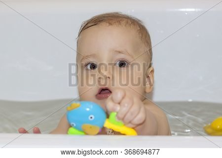 The child is bathing in the bath. Games in the water. Bathing a child. Toys in the bathroom. Portrai