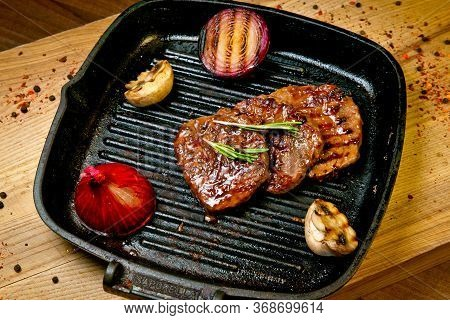 Beef Steak On Grill With Grilled Vegetables In A Frying Pan. On A Wooden Tray