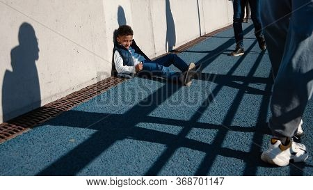 Little Black (african-american) Kid Sitting On The Sidewalk And Look At Passers. Low Evening Sunligh