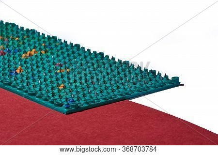 Massager In The Form Of Green Carpet With Metal Spikes, Needles, Lies On Red And White Backgrounds,