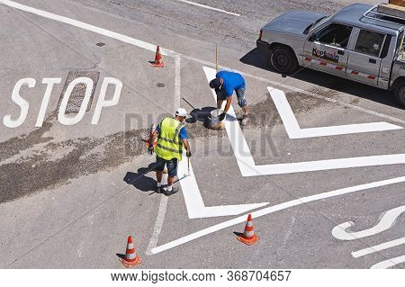 Traffic Line Painting. Workers Are Painting White Street Lines On Crossroads. Refreshment Of Road Ma