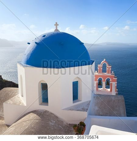 Blue-domed Greek Church And Belfry Against Volcano Caldera In Oia Town On Santorini Island, Cyclades